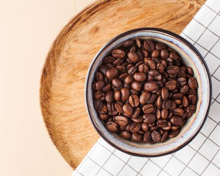 Arabica coffee beans in a ceramic bowl on a wooden tray on a brown background. Horizontal photo with space for text. 版權商用圖片