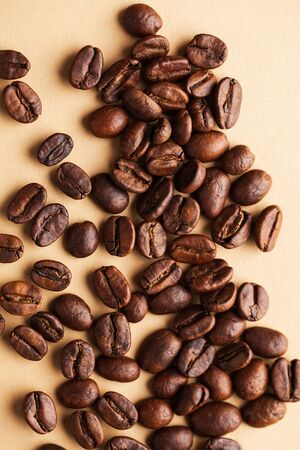Arabica coffee beans close-up on a light brown background. For screensavers, roasters, and coffee sellers.