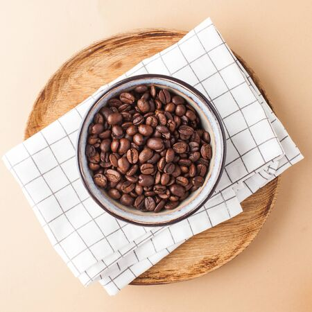 Arabica coffee beans in a ceramic bowl on a wooden tray. Square photo for coffee shops and coffee shops.