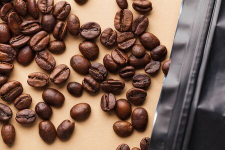 Coffee beans closeup spill out of the package on a light brown background. For roasters, coffee houses and coffee shops.