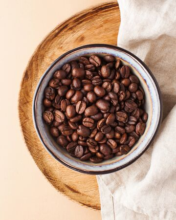 Arabica coffee beans in a ceramic bowl on a wooden tray on a brown background. 版權商用圖片