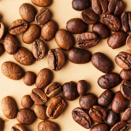 Coffee beans of different varieties close-up on a light brown background. For screensavers, roasters, and coffee sellers. Square photo.