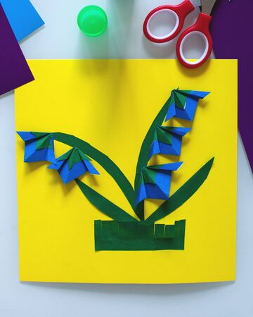 The concept of DIY and children's creativity, a do-it-yourself gift for mother's day. Step-by-step instruction: how to make an application of a blue flower from paper, origami technique. Step 9 finish