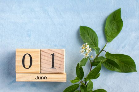 Wooden calendar June 1 on a blue background with white flowers. The concept of the beginning of summer, the first day of June, Children's Day. Banco de Imagens