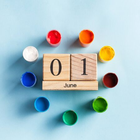 Wooden calendar June 1, surrounded by color paints. World Conference on the Welfare of Children in Geneva, Switzerland, June 1, World Children's Day. Copy space