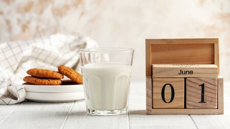 Banner with a glass of milk, a wooden calendar on June 1, homemade cookies. Milk day concept. Copy space. food photo. Foto de archivo