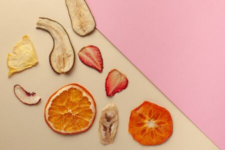 Dried fruit chips on a pink background. The concept of a healthy snack without sugar, dessert for vegetarians. Copy space. Flatlay
