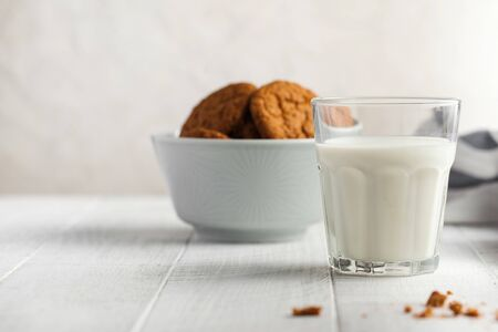 Glass of milk, cookies in a bowl on a light background. The concept of dairy products, farm products, the use of milk, milk day. Banque d'images