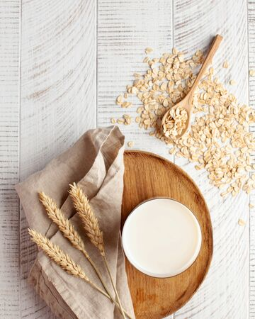 Oat milk in a glass, flakes of baked cereals. Milk substitute, milk for vegetarians. Flatlay. Copy space. High quality photo