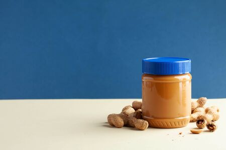 Closed jar of peanut butter on a colored background. American culture. Breakfast, dessert for vegetarians.