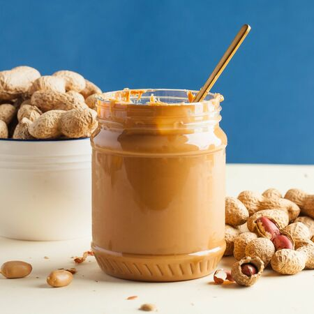 An open jar of peanut butter with a spoon and peanuts in the shell around on a colored background. Quick Breakfast, food for vegetarians. Foto de archivo