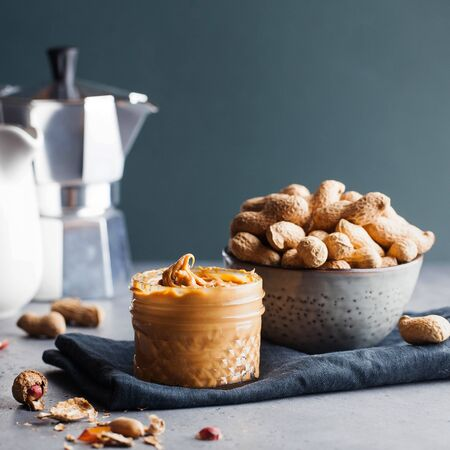 Closeup peanut butter in a glass jar, a handful of peanuts in shell on a gray background. Foodphoto. Copy space. American culture. Breakfast, dessert for vegetarians.