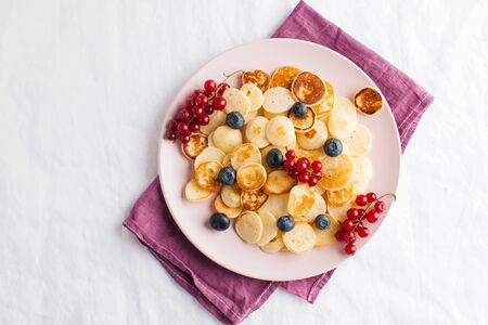 Tiny pancakes with berries, honey on a white tablecloth and space for text. Pancake cereal. The concept of Breakfast, food trends. Copy space. High quality photo