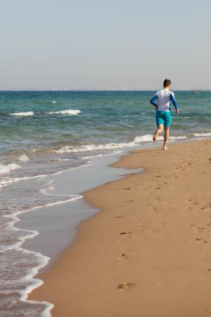 A male athlete runs along the beach in blue shorts along the sea. Coast of Cyprus. Copy space. High quality photo Foto de archivo