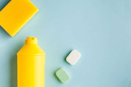 Liquid dishwashing liquid, dishwasher tablets on a blue background. Means for washing dishes. Copy space. Flatlay.