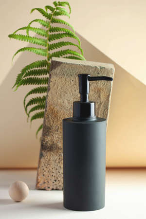 Gray cosmetic dispenser with space for your logo. Spa concept, skin care. Copy space.