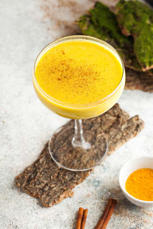 Moon milk for better sleep. Turmeric Golden milk with cinnamon. A trendy relaxing drink before going to bed. Ayurvedic drink. High quality photo Stock Photo