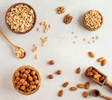 Text frame made of different nuts in wooden bowls. Nuts. Healthy snack. Copy space. High quality photo