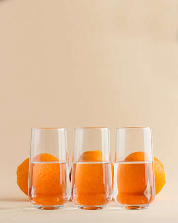 Oranges for glasses of water. Distorted image of water. Art concept, trending photo. Minimalism. Copy space. High quality photo