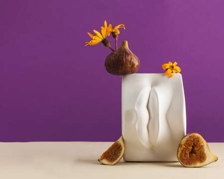 A plaster figure of lips with fresh figs and flowers on it. Art concept