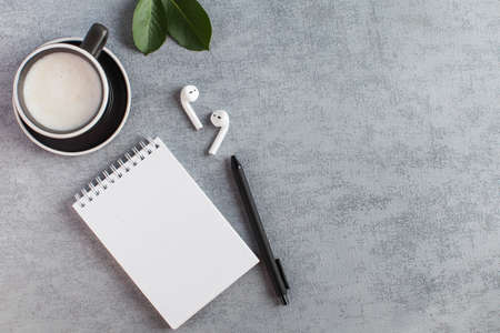 White Notepad, wireless headphones, coffee mug. The concept of online training, work from home, home office. Copy space. High quality photo Stock Photo
