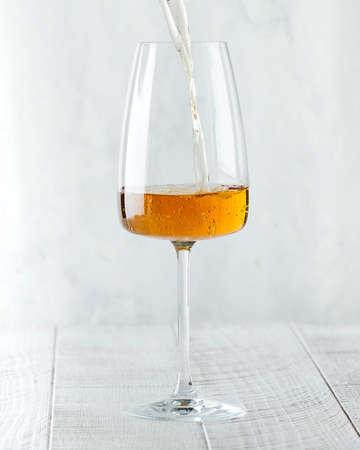 Orange wine is poured into a glass. Winery. High quality photo