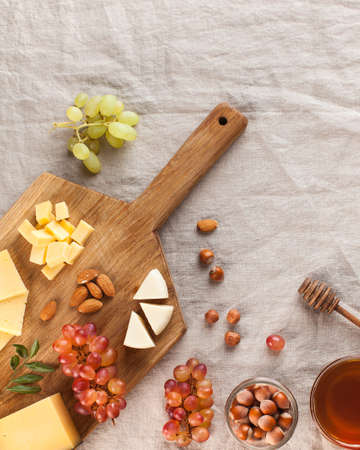 Cheese plate. Assorted cheeses on a wooden Board with grapes, honey, nuts on a linen tablecloth. High quality photo