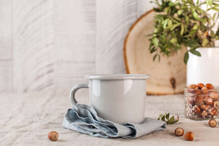 A metal mug on a linen tablecloth. Still life in rustic style. High quality photo