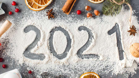 The number 2021 is drawn on flour. The concept of eve 2021, making Christmas cookies. High quality photo