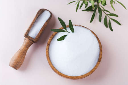 Natural sweetener in a wooden bowl on a pink background. Sugar substitute. Erythritol.