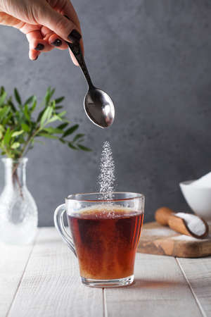In a cup of tea, pour sugar from a teaspoon.