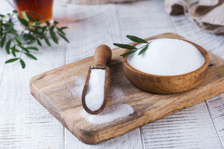 Natural sweetener in a wooden spoon. Sugar substitute. Erythritol