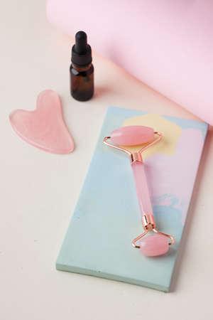 Organic skin care. Rose quartz gua sha stone, jade roller and glass dropper bottle. Eco friendly skincare concept