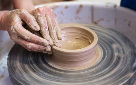 Womens hands make a plate of clay on a potters wheel.