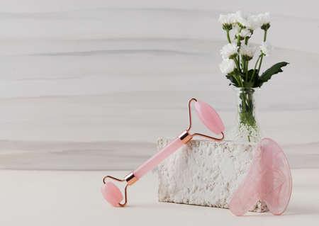 Rose quartz gua sha stone, jade roller on a light background. The concept of home skin care.