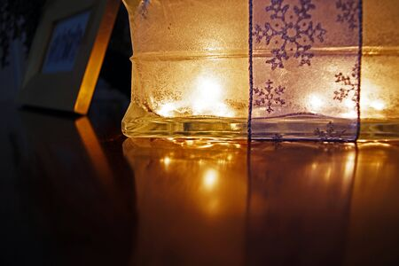 Glass box lit up with reflection glowing on wood table surface