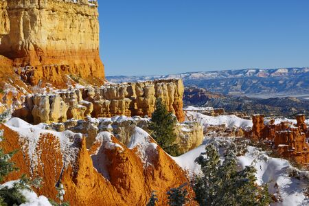 Bryce Canyon Hoodoos displaying their beauty of reds and yellows while surrounded by greens, blues and white