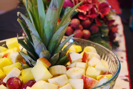Pineapple leaves are adorning a fruit bowl of sliced bananas, apples, pineapple and grapes