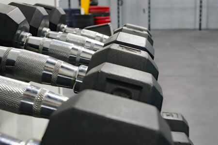 A row of various metal dumbbell weights in a gym Stock fotó