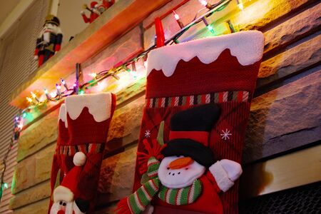 Festive Christmas stockings hanging off the fireplace accented by colored lights 版權商用圖片