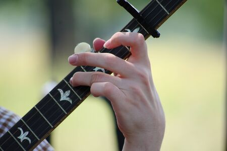 Close up of a human hand playing a banjo