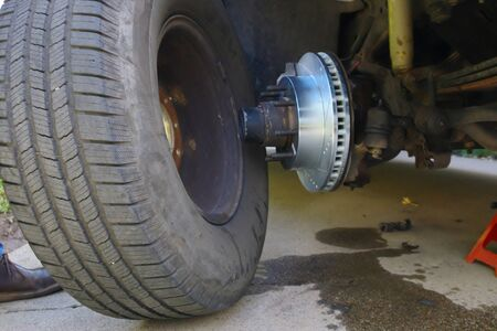 Putting a tire back on the vehicle with the new brakes installed