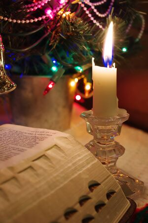 ChristmaReading the Holy Bible by candlelight near the festive lights of Christmas time 写真素材