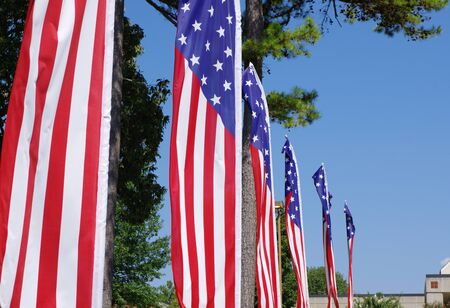 A row of banners in the design of the United States flag against a blue sky Imagens - 131856375