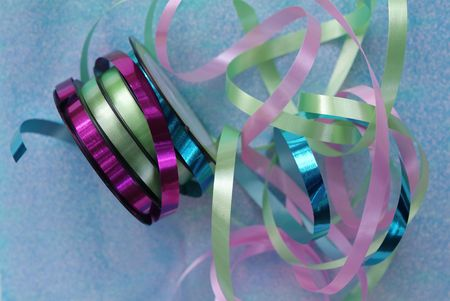 pink, green and aqua blue ribbons unraveling from spool and ready to wrap presents, with blue background Stock Photo - 1298173