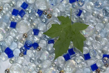 green maple leaf with clear glass marbles and bright blue tiles Stockfoto