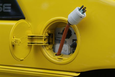 Where the gas tank is usually, there is a plug in this yellow electric car Stock Photo - 1298187