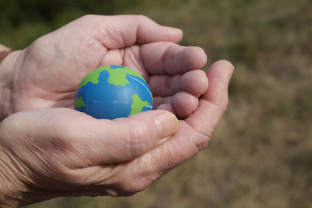 blue and green globe in the palm of hands that are concerned for the environment Stock Photo - 1478905