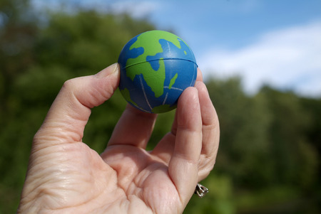 green and blue tiny earth in your fingertips Stock Photo