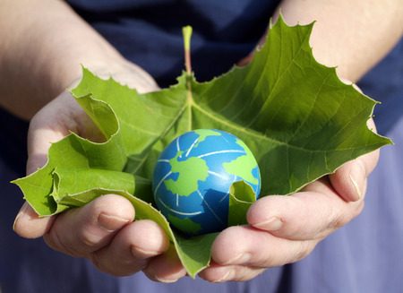 eco friendly: person holding a leaf with small earth  Stock Photo